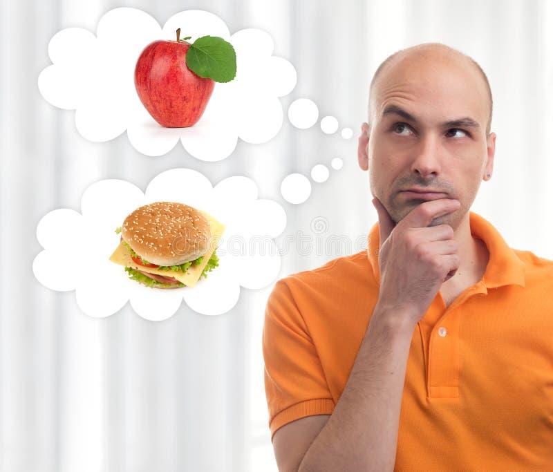 Uomo che sceglie fra la mela ed il panino immagini stock libere da diritti