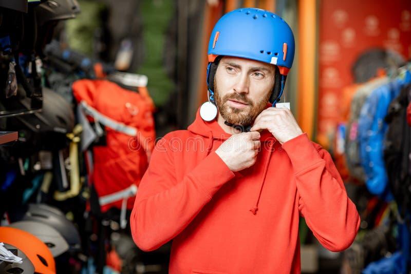 Uomo che sceglie il casco di sport nel negozio immagini stock libere da diritti