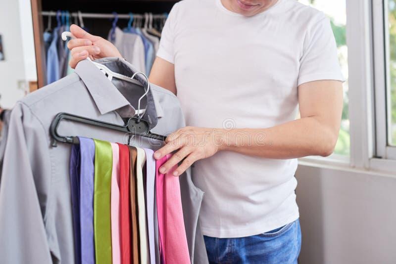 Uomo che sceglie legame per la camicia immagine stock