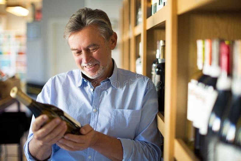 Uomo che sceglie vino fotografia stock