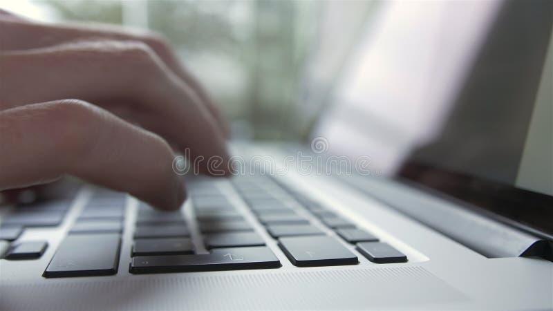 Uomo che scrive e che lavora al computer portatile - vista laterale video d archivio