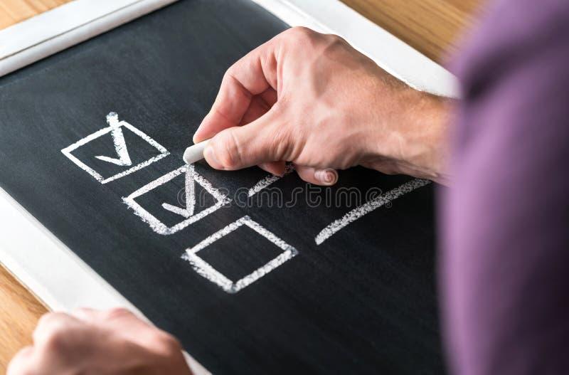Uomo che scrive segno convenzionale alla lista di controllo sulla lavagna Documento di lavoro finito e delle mansioni completate  fotografia stock libera da diritti