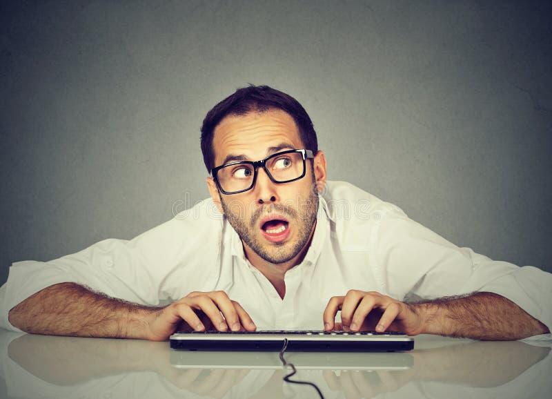 Uomo che scrive sulla tastiera che si domanda circa la risposta fotografia stock