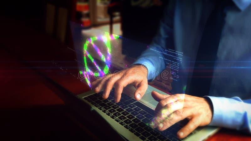 Uomo che scrive sulla tastiera con l'ologramma dell'elica del DNA fotografie stock