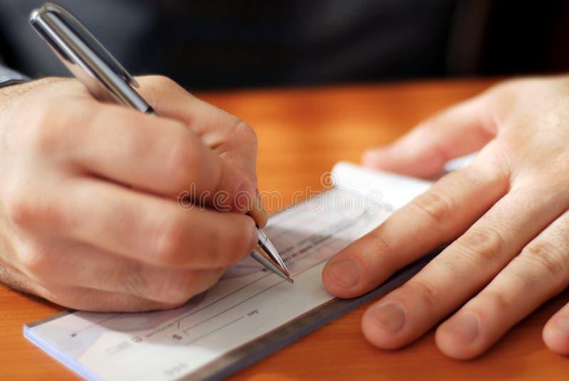 Uomo che scrive un assegno fotografia stock libera da diritti