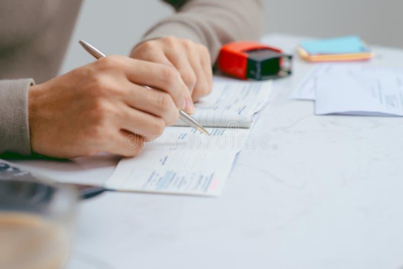 Uomo che scrive un controllo di pagamento alla tavola con il calcolatore e lo sta fotografie stock libere da diritti