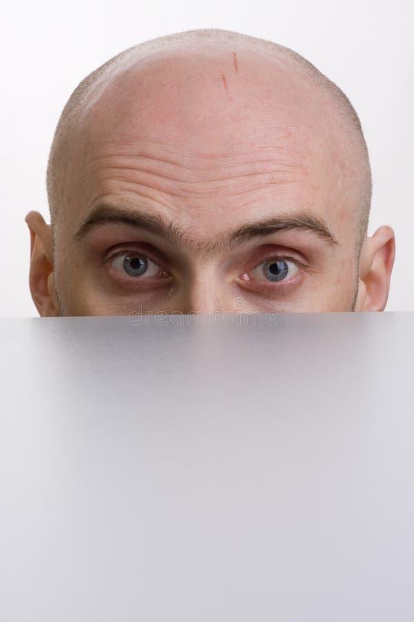 Uomo che scruta sopra un cubicolo immagine stock libera da diritti