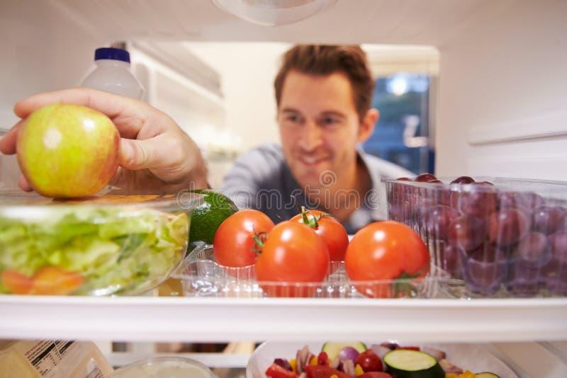 Uomo che sembra frigorifero interno in pieno di alimento e che sceglie Apple fotografia stock libera da diritti