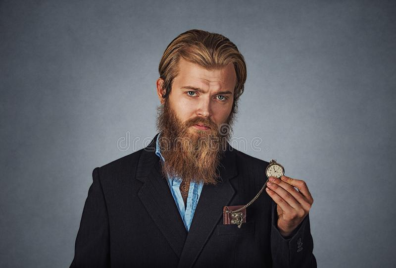 Uomo che sembra serio tenendo retro orologio da tasca fotografia stock