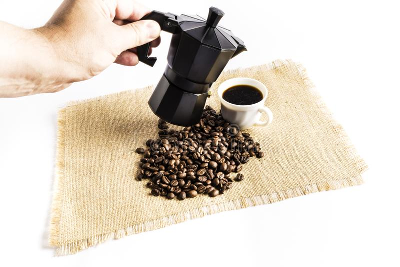 Uomo che serve una tazza di caffè con una macchinetta del caffè italiana accanto ad un mucchio dei chicchi di caffè su una tovagl fotografia stock