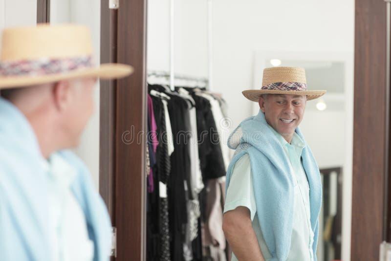 Uomo che si controlla fuori nello specchio fotografia stock libera da diritti