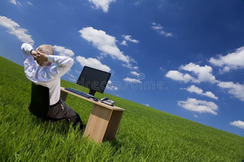 Uomo che si distende alla scrivania in un campo verde fotografia stock libera da diritti