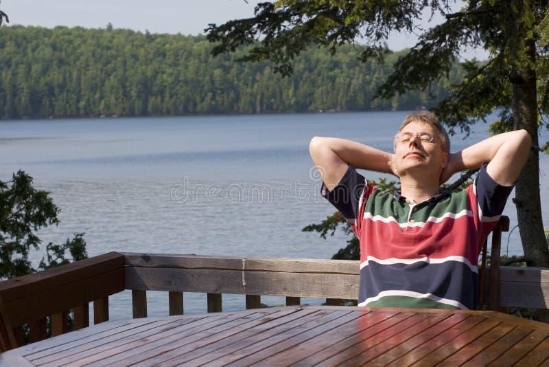 Uomo che si distende da un lago immagini stock