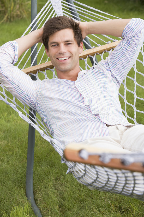 Uomo che si distende nel sorridere del hammock fotografie stock libere da diritti
