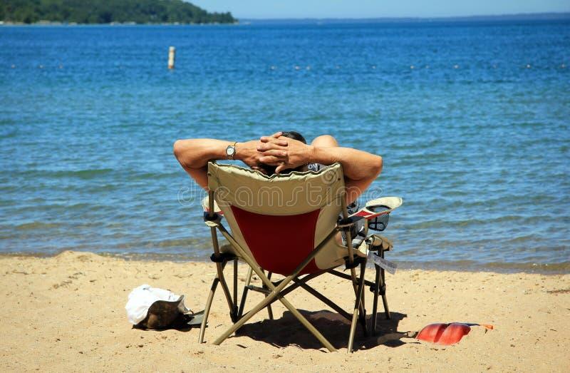 Uomo che si distende sulla spiaggia fotografie stock libere da diritti