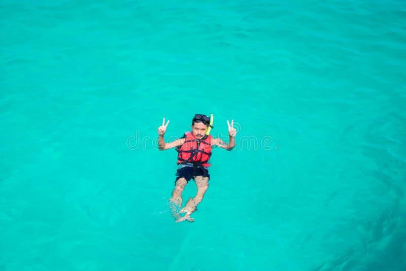 Uomo che si immerge in acqua pulita sopra la barriera corallina immagini stock