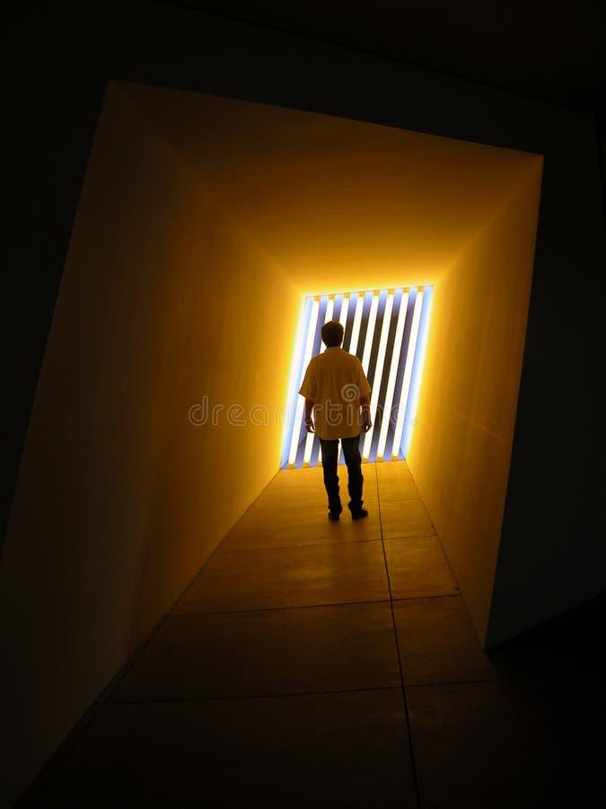 Uomo che si leva in piedi agli indicatori luminosi arancioni fotografia stock libera da diritti