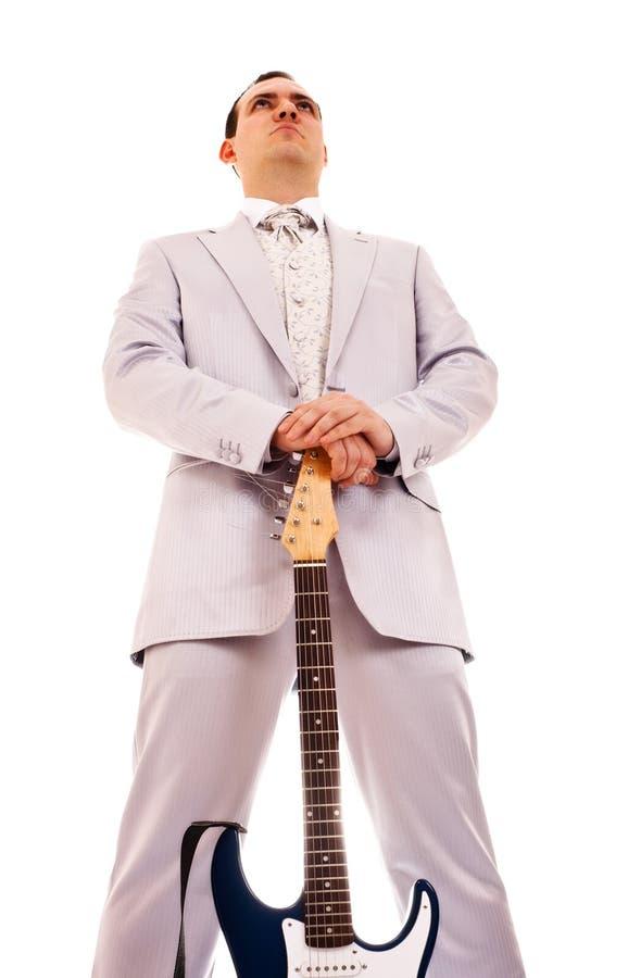 Uomo che si leva in piedi con l'elettro chitarra immagine stock