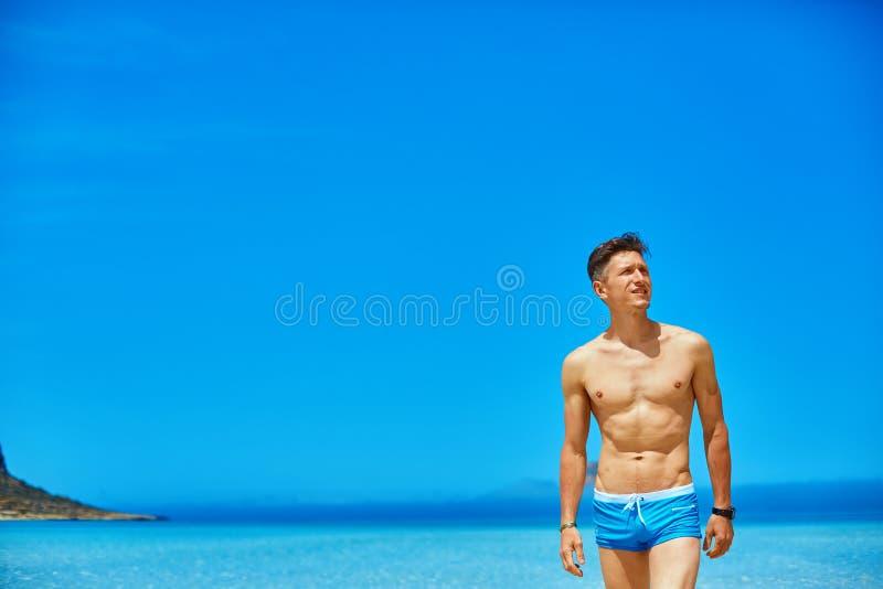 Uomo che si leva in piedi sulla spiaggia immagine stock