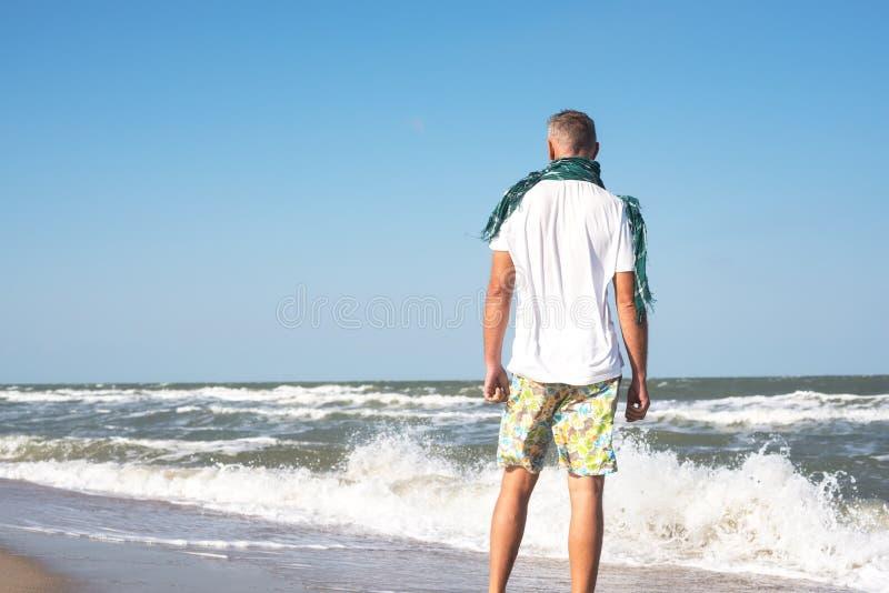 Uomo che si leva in piedi sulla spiaggia immagini stock