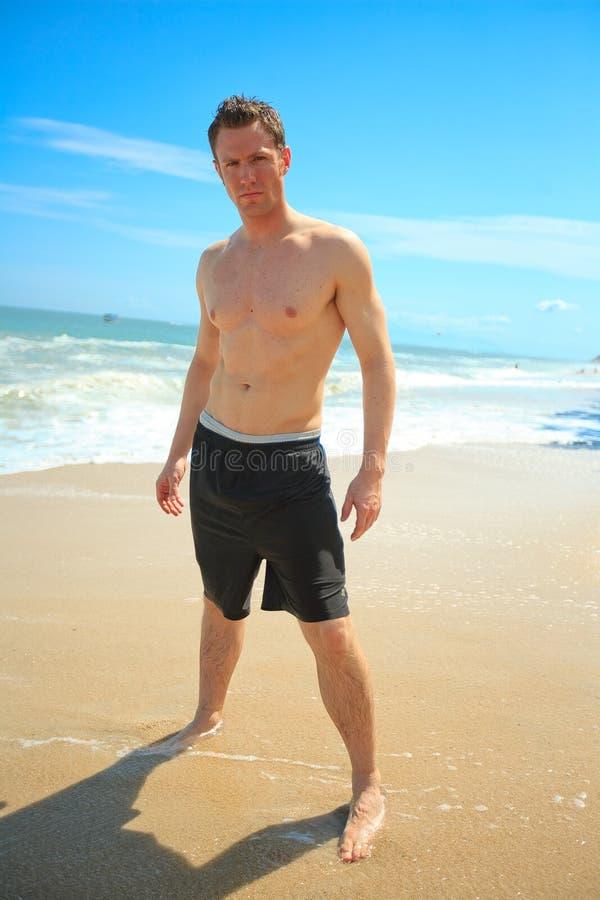Uomo che si leva in piedi sulla spiaggia esotica immagine stock
