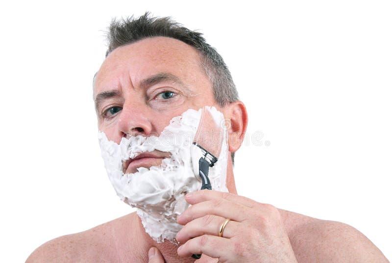 Uomo che si rade con il rasoio fotografia stock