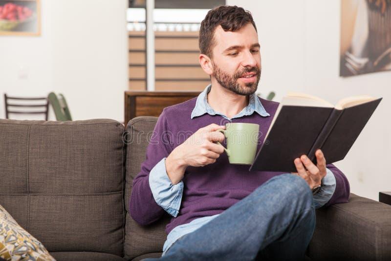 Uomo che si rilassa e che legge a casa fotografie stock libere da diritti