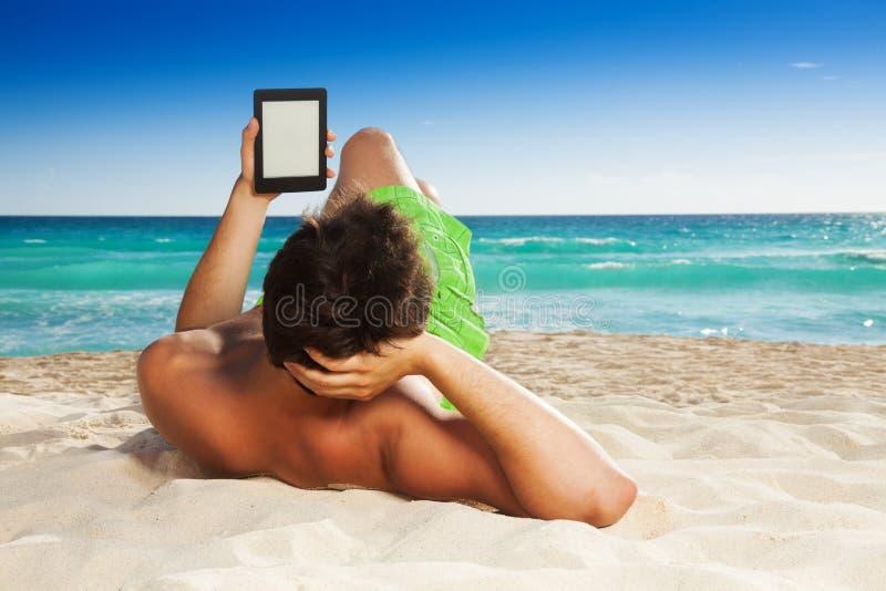 Uomo che si rilassa sul libro elettronico della lettura della spiaggia fotografia stock
