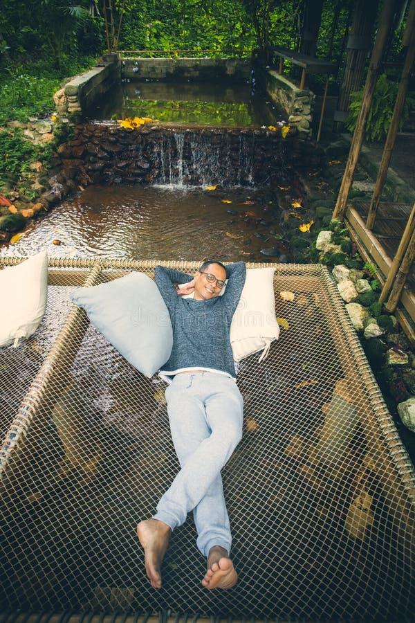 Uomo che si rilassa sulla culla netta sopra insenatura scorrente, vacanza che viaggia nella foresta pluviale tropicale immagini stock