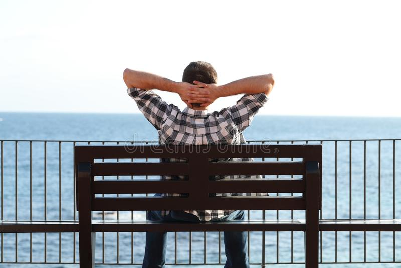 Uomo che si rilassa sulla spiaggia che si siede su un banco immagini stock