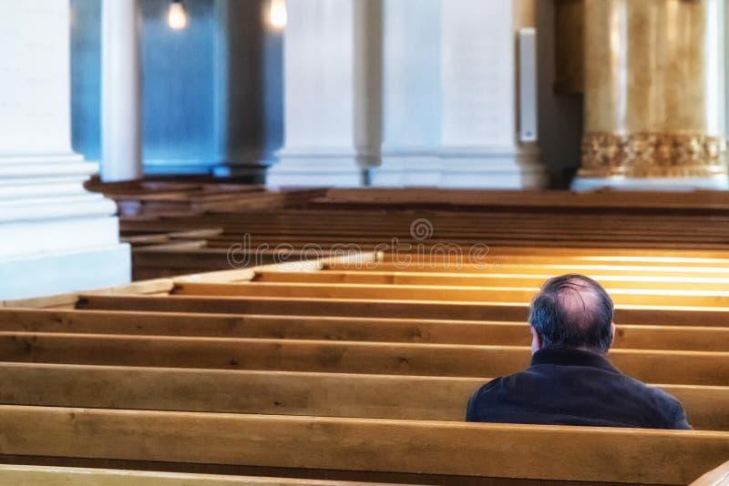 Uomo che si siede alla chiesa fotografia stock libera da diritti