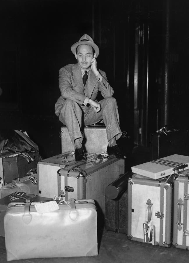 Uomo che si siede con i bagagli (tutte le persone rappresentate non sono vivente più lungo e nessuna proprietà esiste Garanzie de fotografie stock libere da diritti