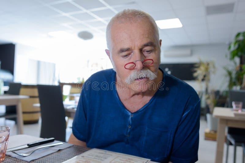 Uomo che si siede da solo nel pub e che legge menu immagini stock libere da diritti