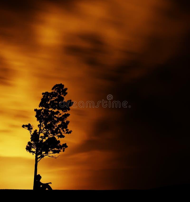 Uomo che si siede da Tree fotografie stock libere da diritti