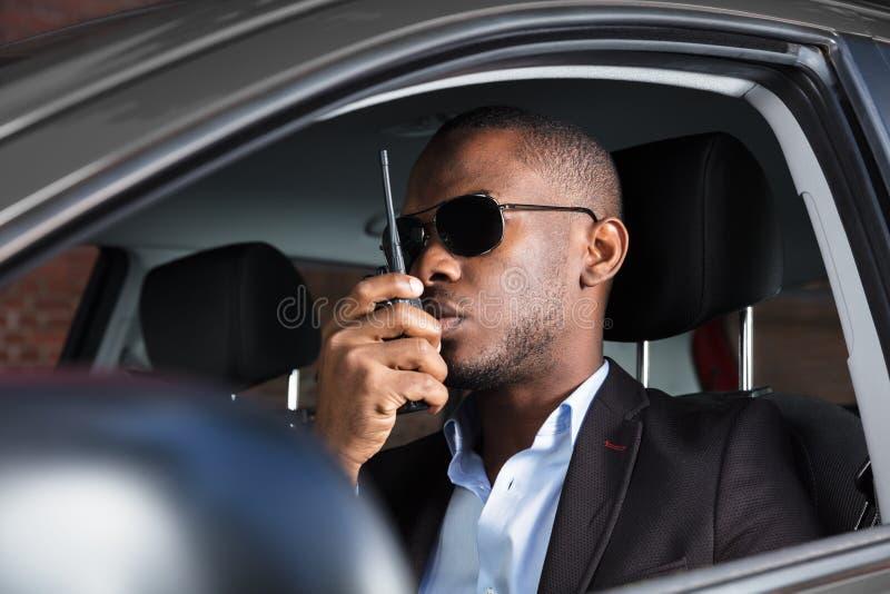 Uomo che si siede dentro l'automobile che parla sul walkie-talkie fotografie stock