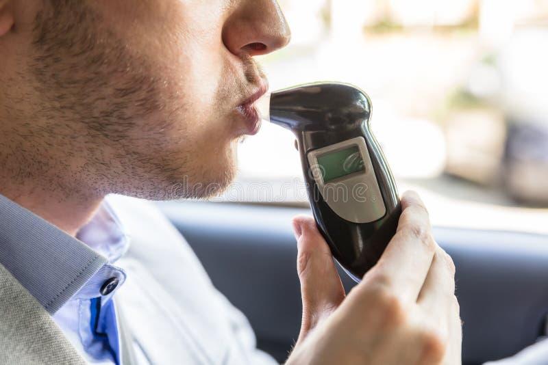 Uomo che si siede dentro l'automobile che prende l'esame all'alcool fotografie stock