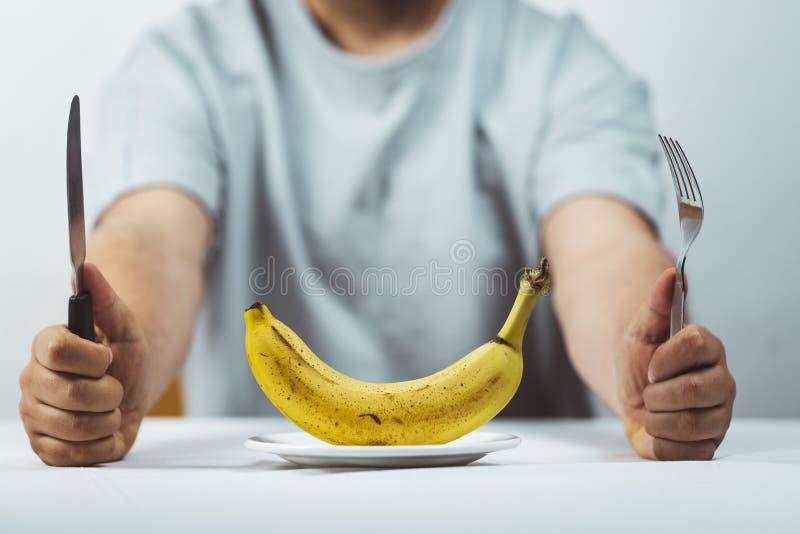 uomo che si siede dietro una tavola con la forcella ed il coltello nelle mani ed in una banana fresca su un piatto su una tavola  immagine stock libera da diritti