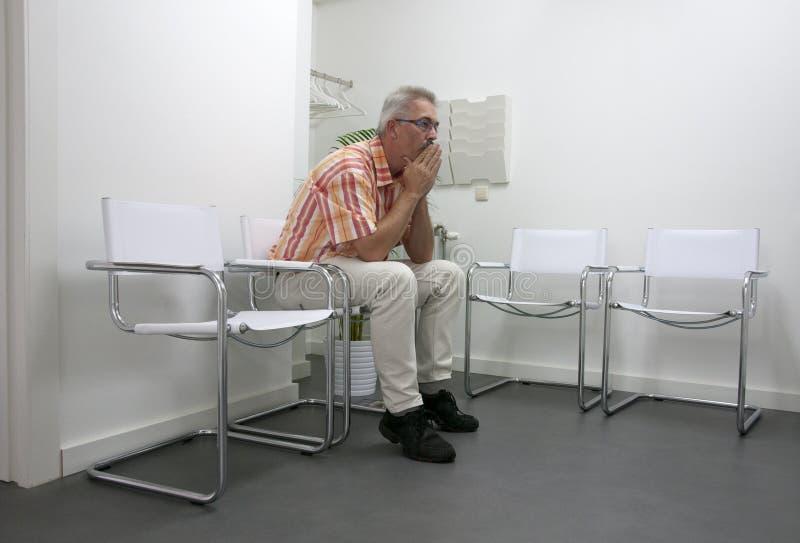 Uomo che si siede e che attende nel waitingroom immagini stock