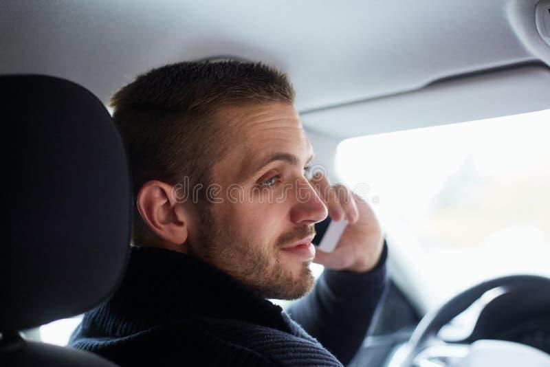 Uomo che si siede nell'automobile e nelle chiamate immagine stock