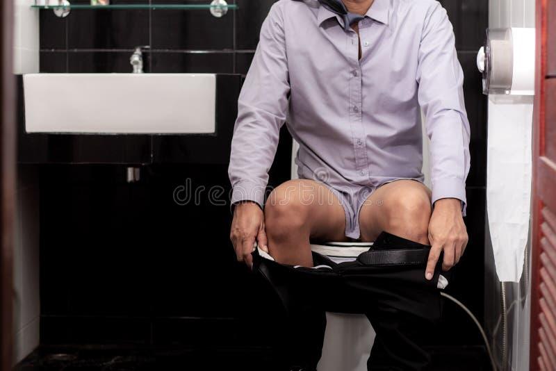 Uomo che si siede nella toilette immagini stock libere da diritti