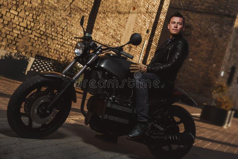 Uomo che si siede su un motociclo del caffè-corridore fotografia stock