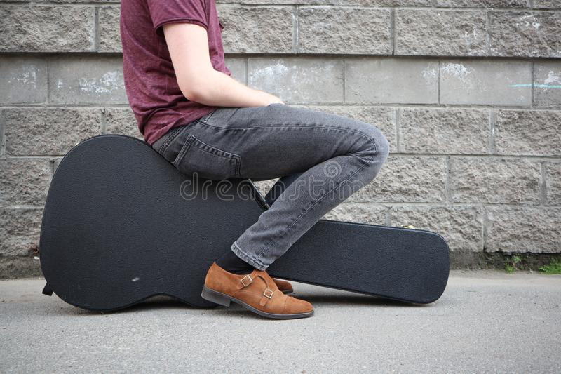 Uomo che si siede su una cassa nera della chitarra Cassa dura per la chitarra elettrica immagine stock libera da diritti