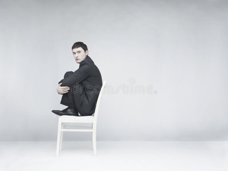 Uomo che si siede su uno sgabello bianco fotografia stock libera da diritti