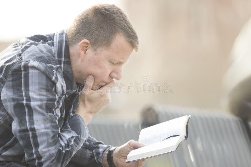Uomo che si siede sul banco e che legge bibbia fotografie stock