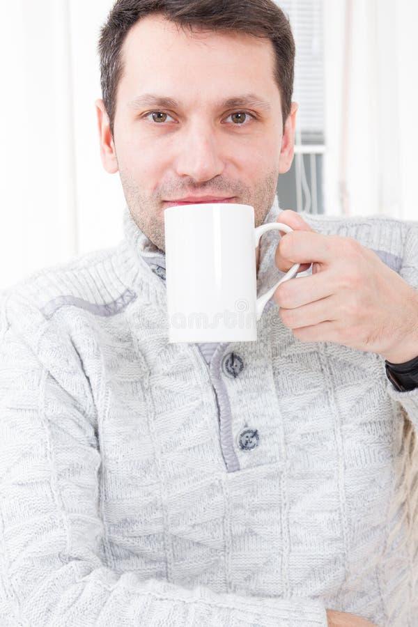 Uomo che si siede sul caffè bevente della sedia che si rilassa a casa fotografie stock libere da diritti