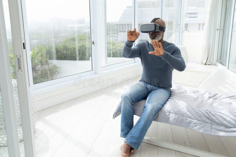 Uomo che si siede sul letto mentre usando gli occhiali di protezione virtuali fotografie stock libere da diritti