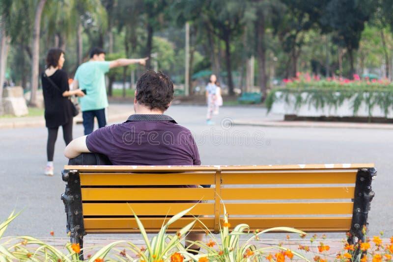 Uomo che si siede sul parco del banco fotografie stock libere da diritti