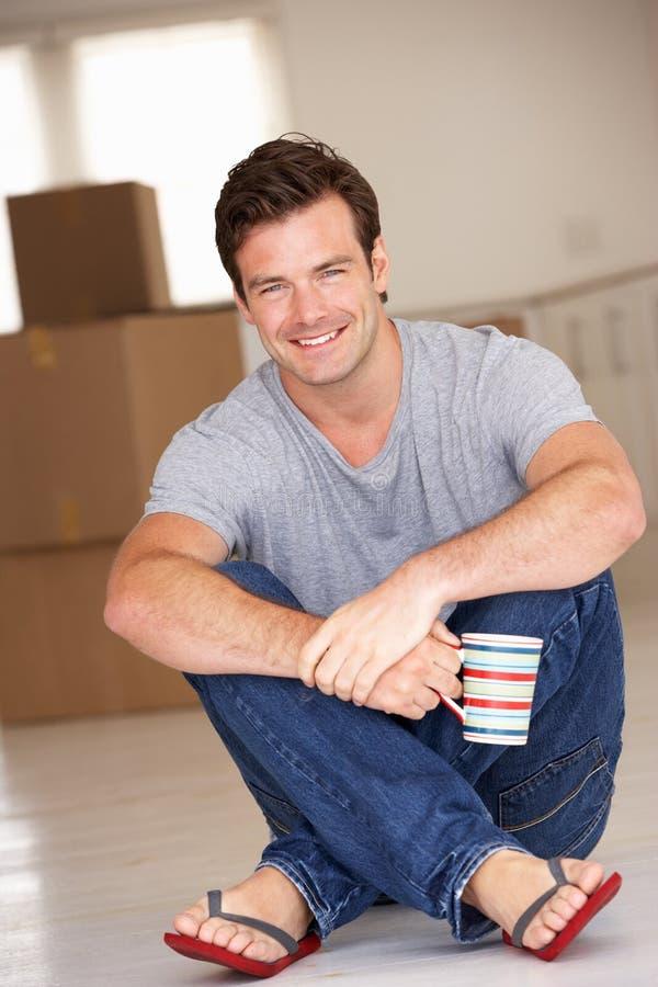 Uomo che si siede sul pavimento nella nuova casa   fotografia stock libera da diritti