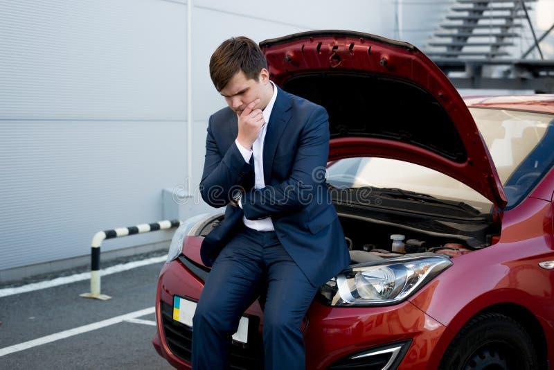 Uomo che si siede sul ribaltamento del cofano a causa dell'automobile rotta immagini stock