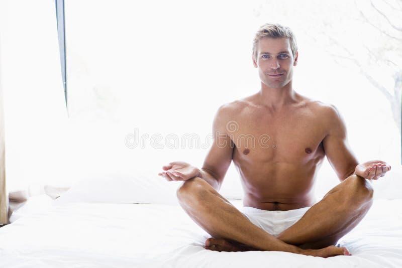 Uomo che si siede sulla base che fa yoga fotografie stock